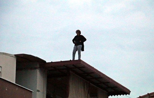 Hakkında arama kararı bulunan kadın, polisi görünce çatıya çıktı